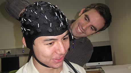 Dan fitting an EEG cap on Bowen's head